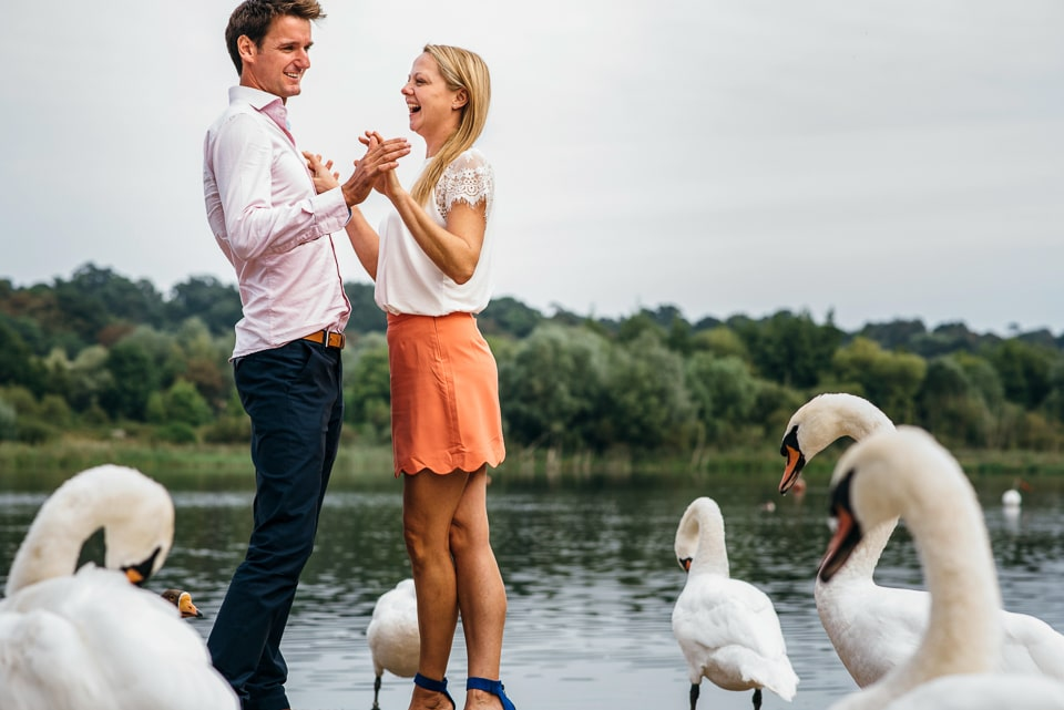 Two people holding each other being photographed surrounded by swans
