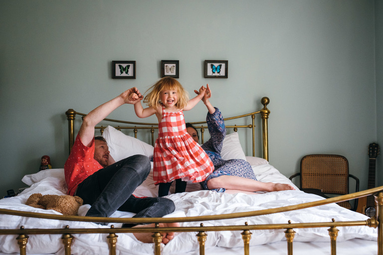 little girl jumping on the bed family photography