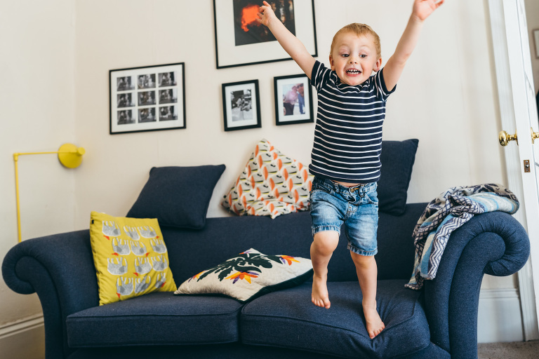 young boy jumping of the family sofa