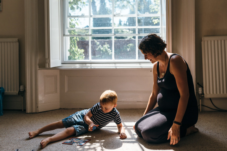 pregnant mother and young boy put a puzzle together by a window